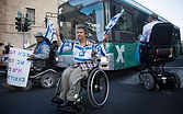 An older white presenting Jewish woman sits in her manual wheelchair in front of a city bus. She is wearing 3 Isreali flags pinned to her shirt and holding another in her left hand.