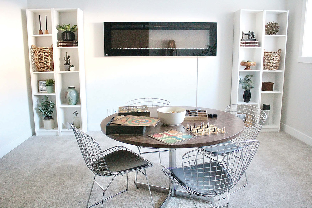 DIY Games Room Makeover   White Cabinets Surround Wall Mounted Fireplace with a Round Table in the Centre of the Room
