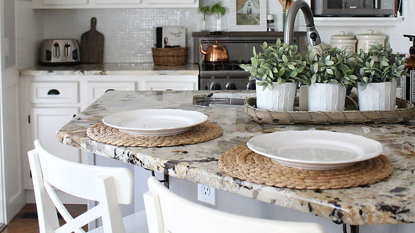 Kitchen countertop with white plates set on round bamboo table mats.