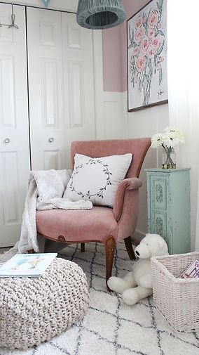 Pink accent chair piece over plush area rug.