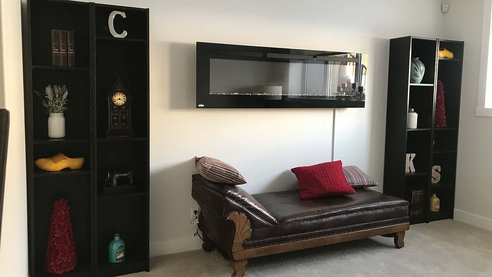 Before Seating Area in Basement   Wall Mounted Fireplace and Dark Shelving