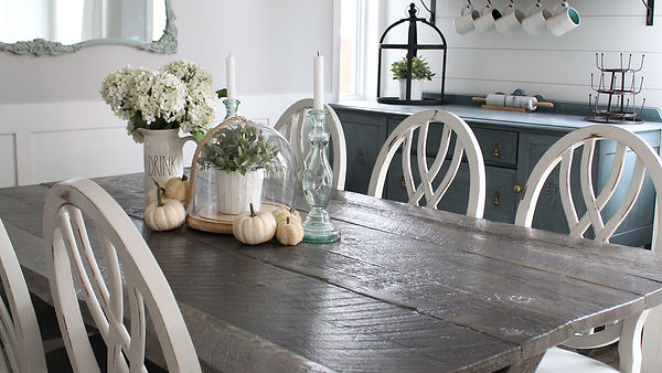 Light grey table wih white chairs, complimented with fall themed decor of whte flowers and white pumpkins.