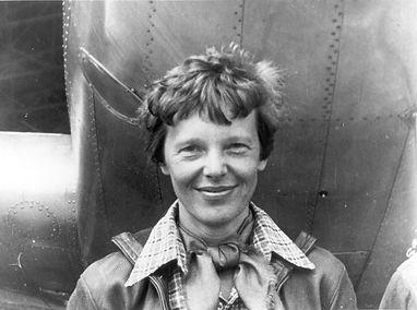 Amelia_Earhart_standing_under_nose_of_he