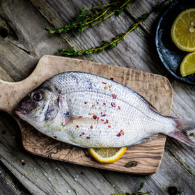 Fresh sea bream on wooden board.jpg