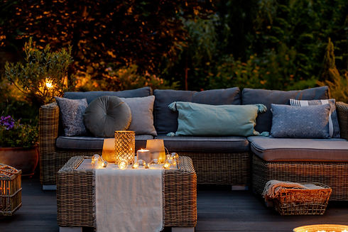 Warm summer night in the garden with trendy furniture, lights, lanterns and candles.jpg