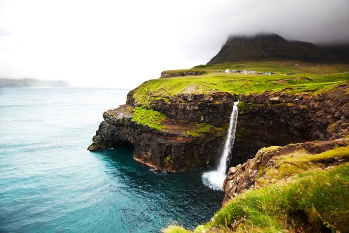A spectacular view on the waterfall on the cliff taken on a trip to the Faroe Islands