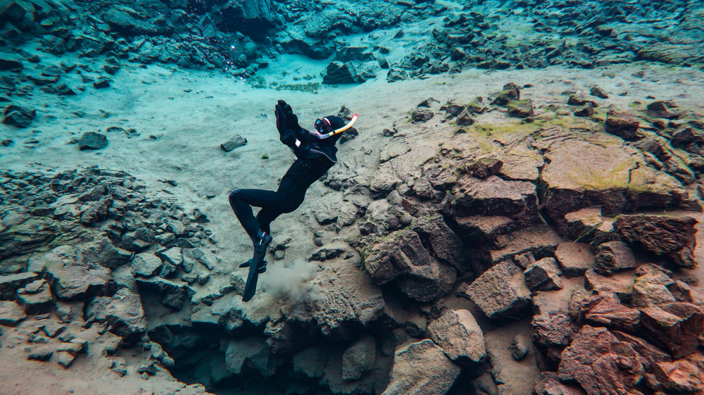 A woman enjoying Silfra snorkeling in Iceland in a wetsuit