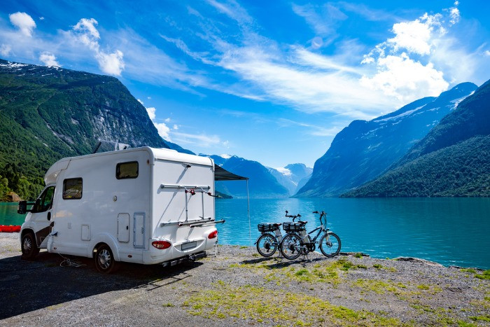 A family camping in Norway with an RV near the lake with the mountains in the background