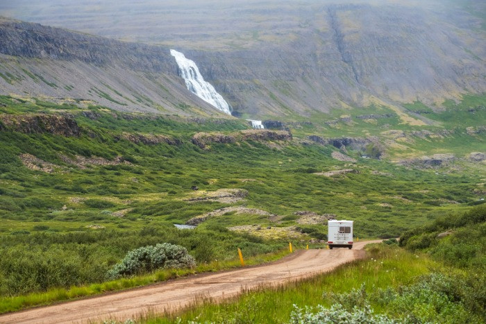 A view of an RV going down the road towards Dynjandi Waterfall in Iceland