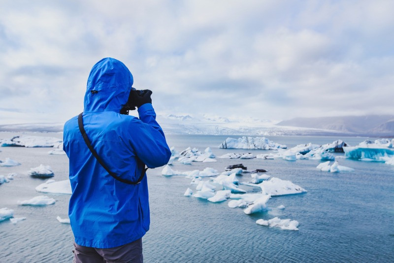 A tourist enjoying Jokulsarlon lagoon in April in Iceland
