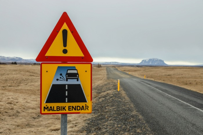 A road sign on a gravel road in Iceland warning of ending of the asphalt road