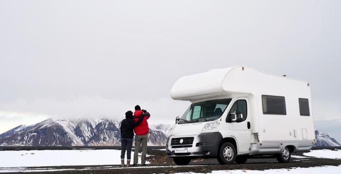 Turists enjoying their motorhome rental in Iceland admiring the winter landscape