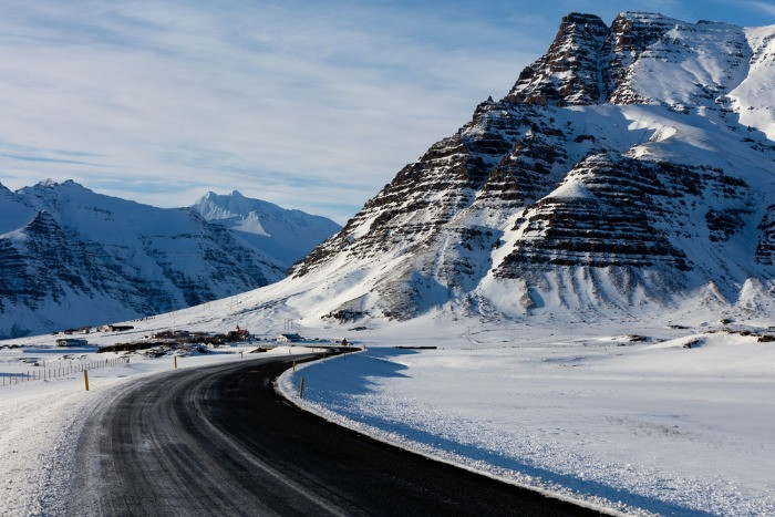 Typical Icelandic road covered with snow, leading to a tall mountain all covered in ice and snow