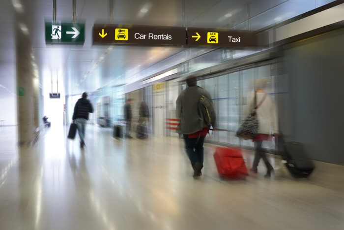 Airlines passengers goind down the airport in car rental ofices direction