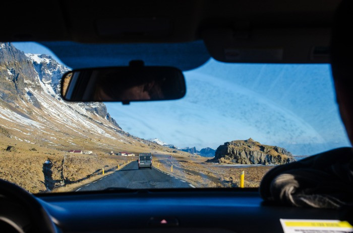 Turist driving a motorhome rental on paved road in Iceland with beautiful landscapes around