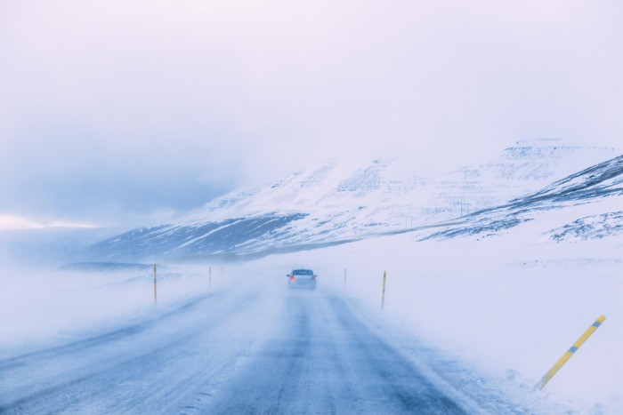 A car driving in witner road in Iceland with the mountains covered with snow