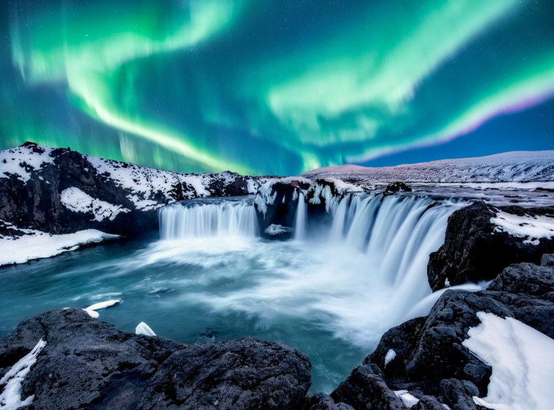 An amazing view over the Godafoss waterfall with the Northern Lights in winter. Camping and caravanning in Iceland in winter!
