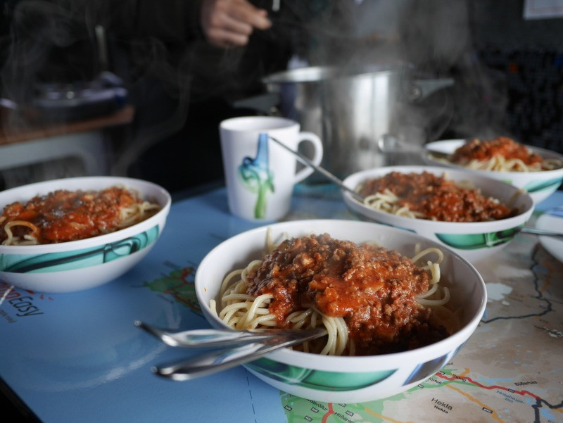 Bowls of spaghetti on a table. Cooking in a motorhome advantages of a road trip in Iceland.