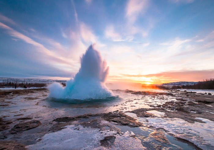 Stokkur geyser with a sunset in the background in the Golden Circle in Iceland