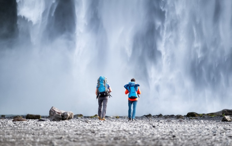 Couple of tourists in front of a waterfall, planning their extreme activities in Iceland