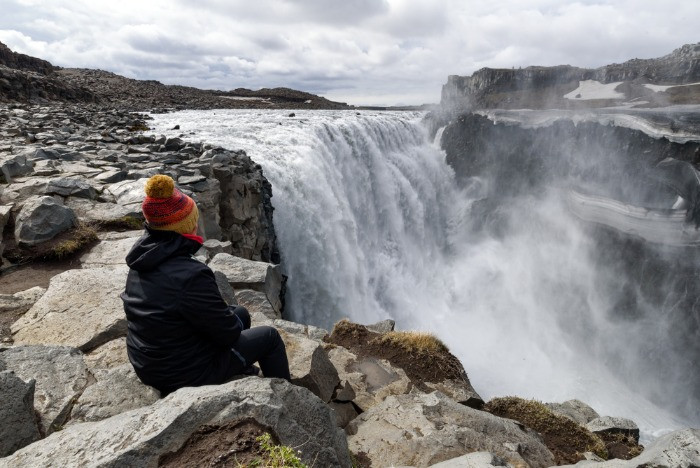 A female tourist sitting at the edge of the Dettifoss waterfall