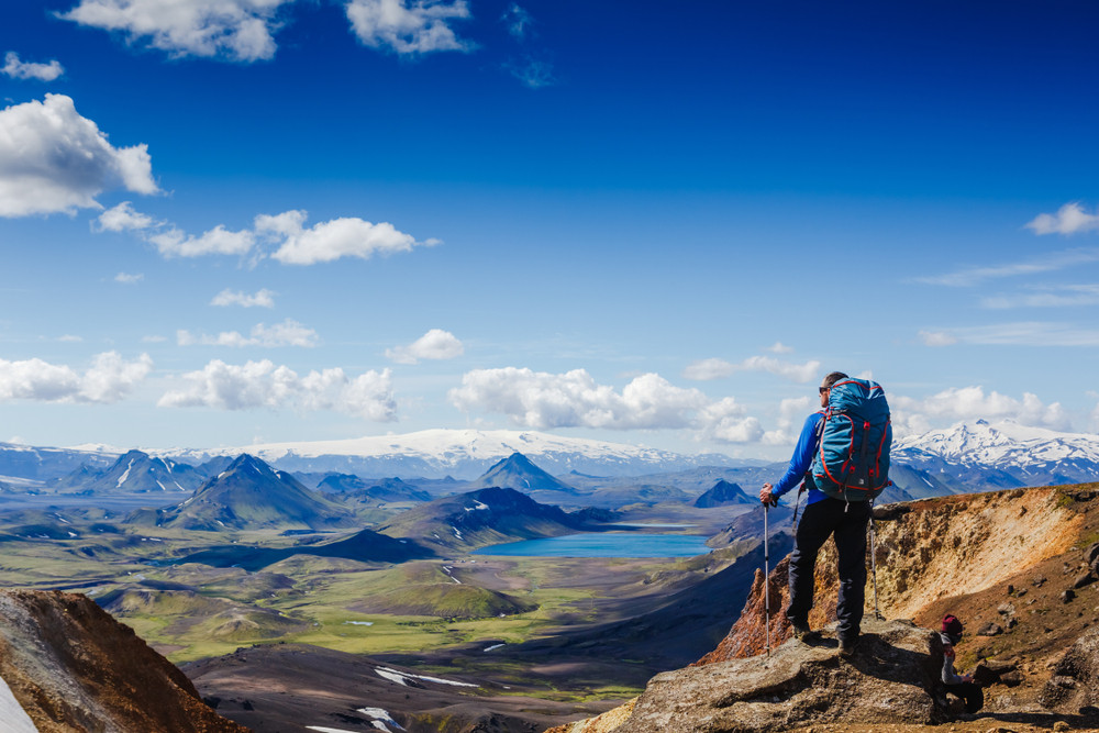 Tourist admiring beautiful landscapes from the popular hiking trail in Landmannalaugar