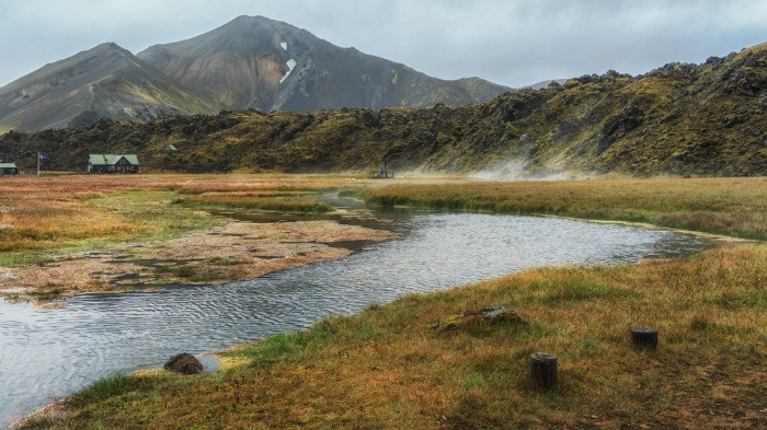 A view on hot springs with a wooden Landmannalaugar hut in the background