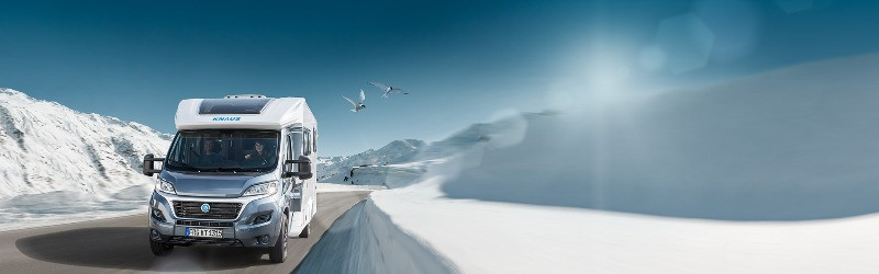 RV rental on Icelandic road in winter with the snow covering the sides of the road