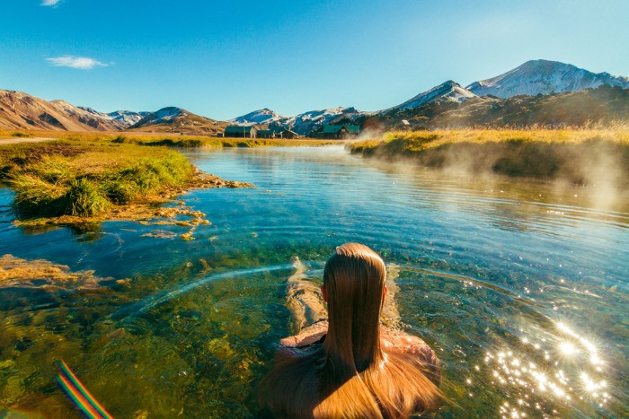 A female haveing a swim in a hot spring in Landmannalaugar on a sunny day, with a agnificent view over the mountains
