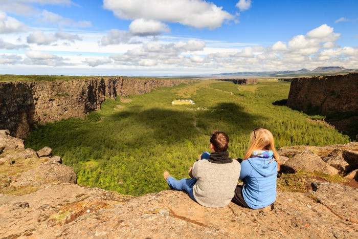 A couple of tourists admiring the view on the Asbyrgi Canyon in Iceland in a sunny summer day