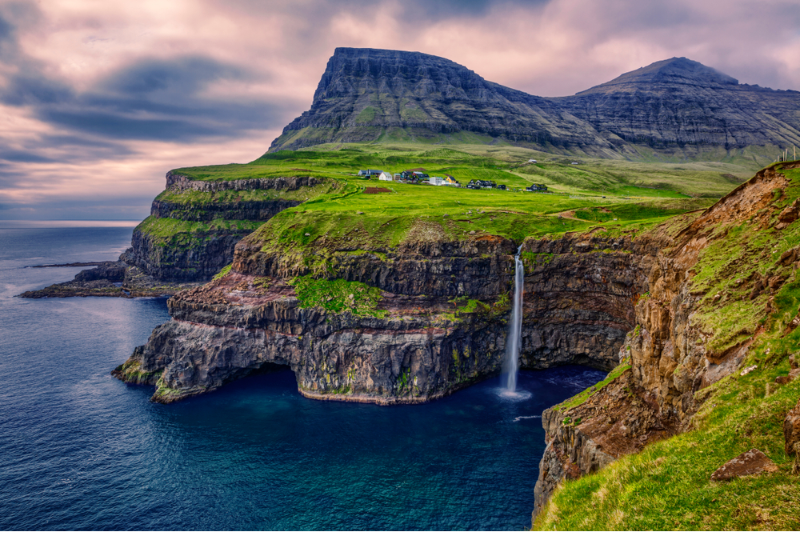 A view ver the cliff with waterfall falling down the rocks on the Faroe Islands