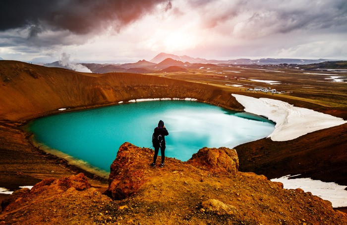 Male tourist observin an amazing view on Viti Volcano lake with deep blue water