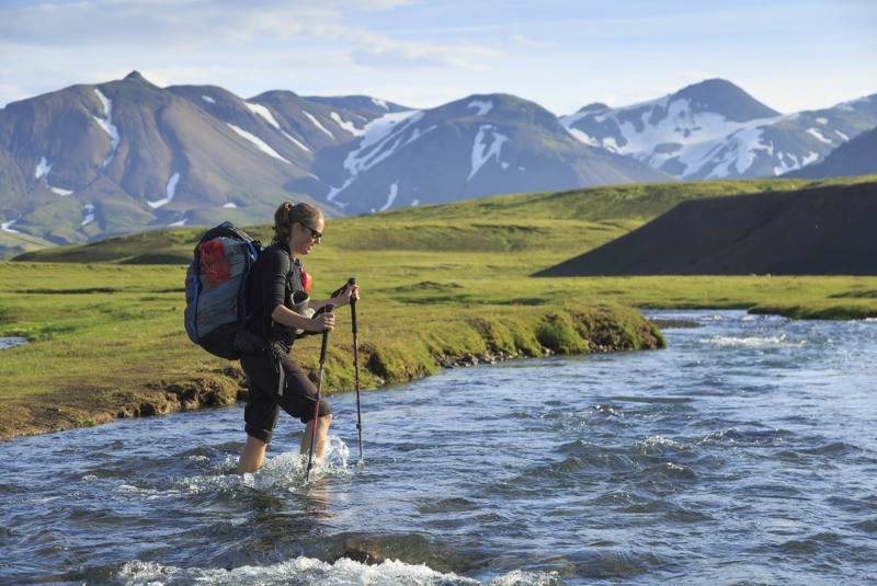 A woomen crossing the river on the Laugavegur hiking trail in Iceland's Highlands