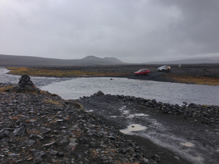 A group of two cars crossing river in Askja