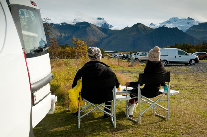 A couple having their meal on a campsite in Iceland with their rented campervan, looking at the picturesqua landscape