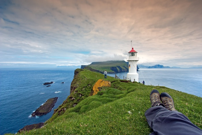 A male tourist having rest on a green grass during his trip to the Faroe Islands