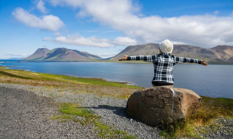 An elder woman admiring landscapes during her tours in Iceland for seniors