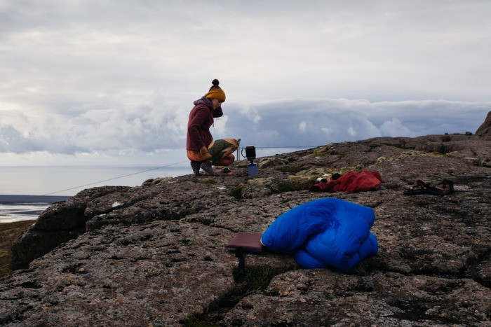 A female tourist making her meal on camping in Iceland with the sea on the background