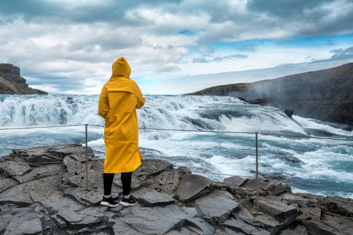 A femal tourist in a yellow raincoat looking at the Gullfoss, in a cloudy day