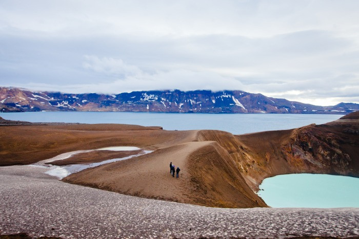 Tourists standing on the edge of Viti Volcano crater in Askja, admiring the view of the volvanic area