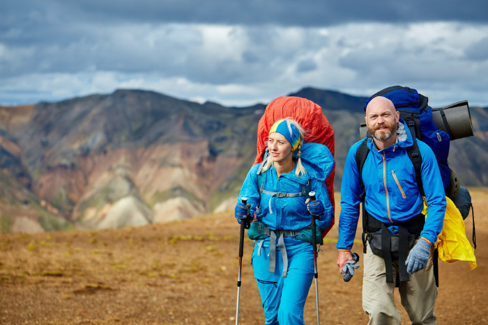 A couple of tourists hiking in Landmannalaugar fully dressed in trekking clothes