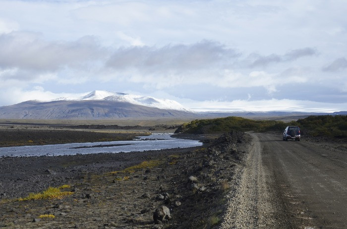A 4x4 rental car on a gravel road in Iceland with mountains covered in snow in the background