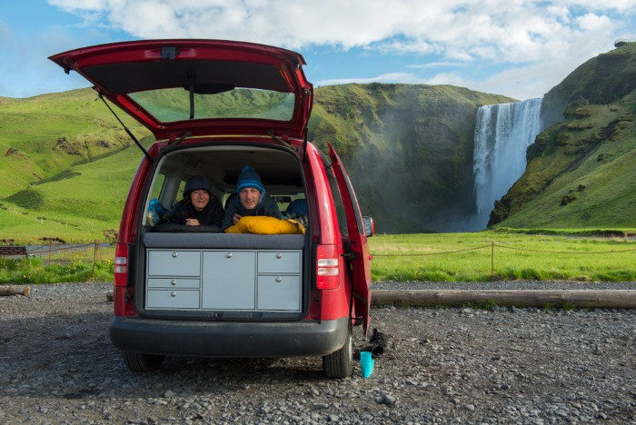 A happy couple in a 4x4 camper van in Iceland with Skogadoss waterfall in the background