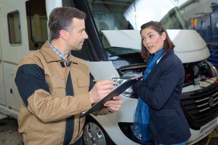 A Female tourist checking with the agetn for bes deals on RV rental in Iceland