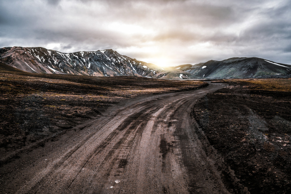 Icelandic F-roads with the sun setting behind the snowy mountains