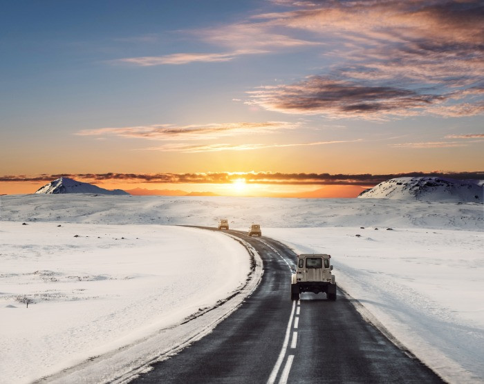 Rental campervan on the Icelandic road in winter at the sunrise, winter landscape