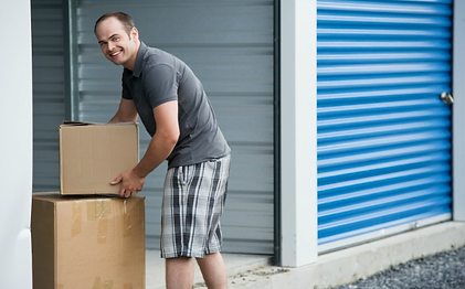 Man loading boxes into storage unit.