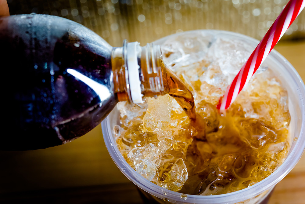 Soda pop being poured into cup with ice and straw