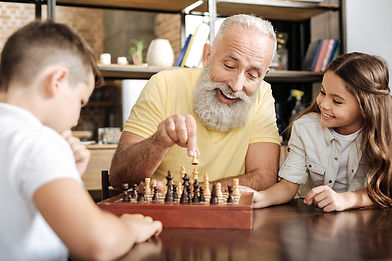 old man and grandchildren playing chess.