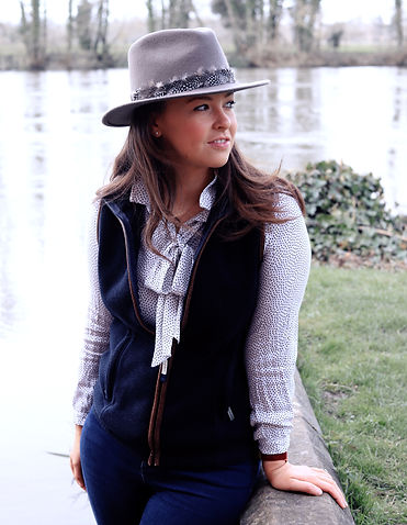 Woman wearing a grey fedora hat sat by the river in a navy blue schoffel gilet and spottey blouse